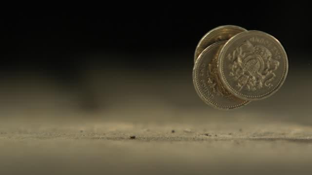 vídeos de stock e filmes b-roll de high speed three uk pound coins roll through frame - moeda de cinco cêntimos