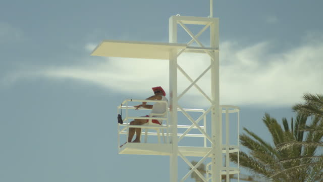 high speed tilt down to lifeguard sitting in high chair, spain. (individual frames may also be used as a still image. each frame in its raw state is about 6mb or about 12mb as a 16 bit tiff) - lifeguard chair stock videos & royalty-free footage
