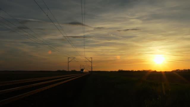 vidéos et rushes de high speed train passing by at sunset - voie ferrée