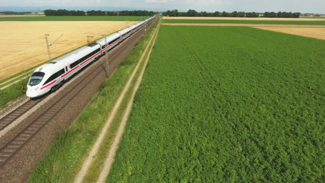 high speed train passing through countryside flyover - schienenverkehr stock-videos und b-roll-filmmaterial