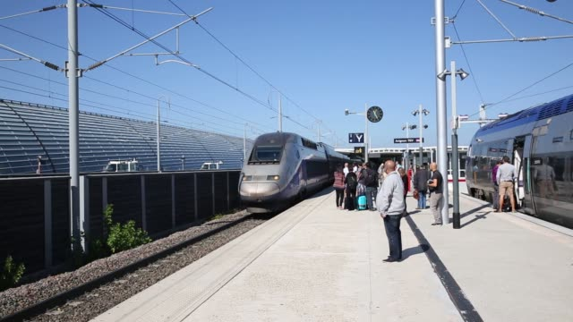 A TGV high speed train pulls up to the platform at the train station in Avignon France Commuters wait on the train platform for the high speed train...