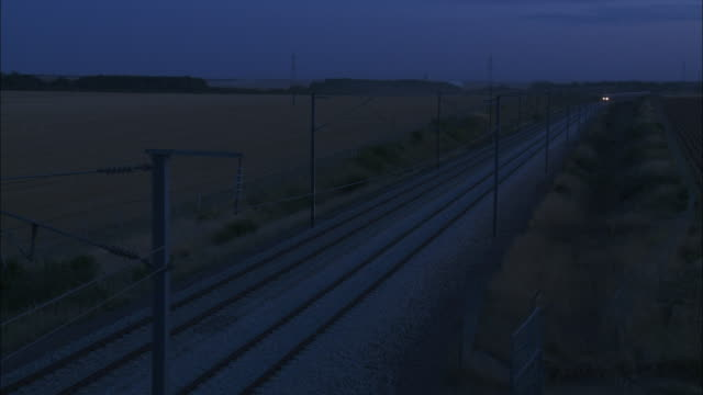 A high speed train races through the French countryside at night.