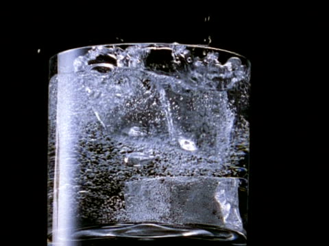 High Speed Two ice cubes fall into glass of fizzy water, black background, fizzy water bubbling  (filmed at between 250-500fps)