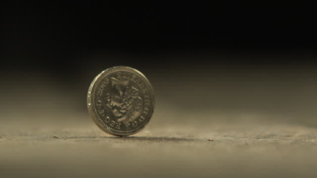 vídeos de stock e filmes b-roll de high speed uk one pound coin falls, spins and finally settles on surface - sorte