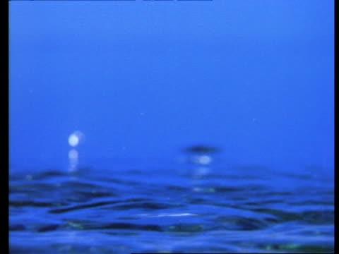 high speed - water drop falling, forming corona, blue background - splashing droplet stock videos & royalty-free footage
