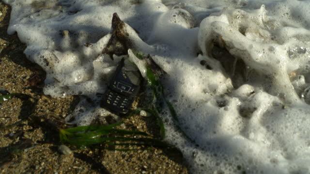 vídeos de stock e filmes b-roll de high speed waves washing over mobile phone on beach - abandoned