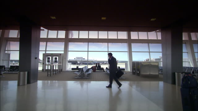 High speed wide shot businessman at airport gate walking and talking on mobile phone/ Seattle