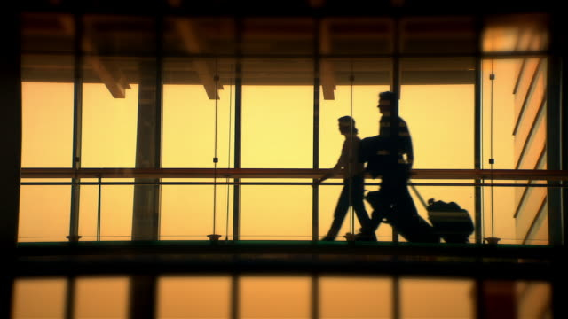 High speed wide shot young couple pulling luggage down corridor/ Seattle, Washington