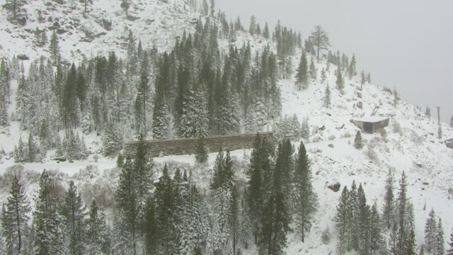 WS ZO AERIAL POV High stone wall on hillside near tunnel entrance in snow covered pine forest in northern Sierra Nevada / Truckee, California, United States