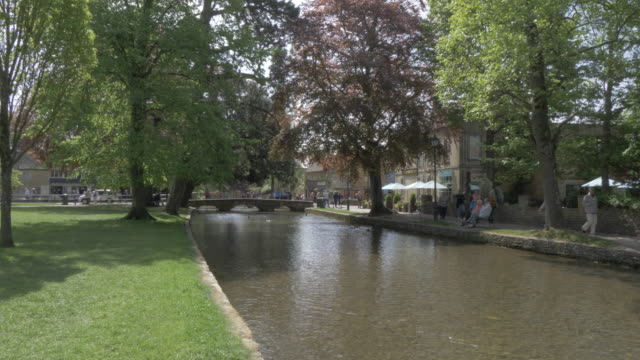 high street and bridge over river windrush in bourton on the water, cotswolds, gloucestershire, england, united kingdom, europe - windrush river stock videos and b-roll footage