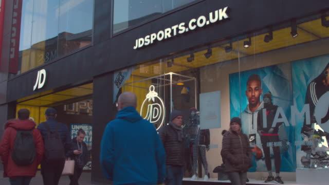 vídeos de stock e filmes b-roll de high street shopping, chrismas shopping retailers, jd sports fashion plc uk shopfront branding - roupa desportiva