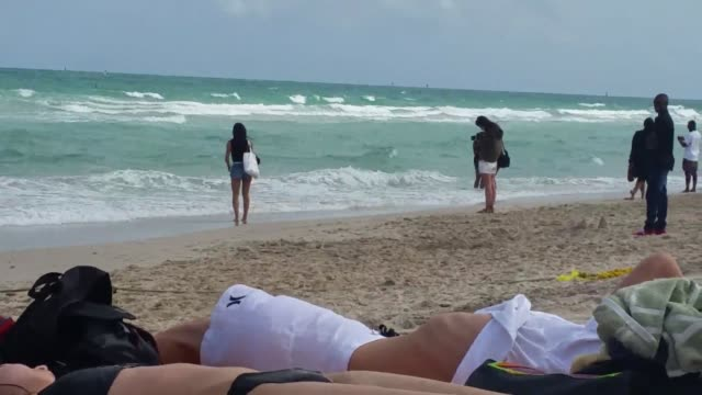high surf/rip currents warning didn't deter tourists and beach-goers from enjoying a sunny mid-winter day in miami, florida. - one piece swimsuit stock videos & royalty-free footage