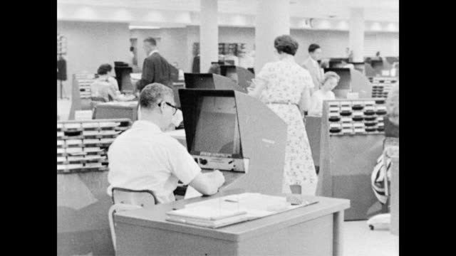 vidéos et rushes de / high tech modern office full of busy men and women / men sit in front of microfiche machines as women walk around. at the social security insurance... - politics and government