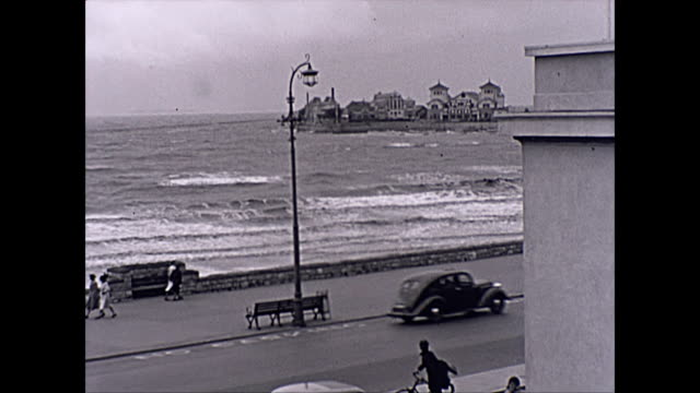 high tide at weston-super-mare marine parade 1949 / vintage street light / people walk along the parade / waves crash against the sea wall opposite... - 1940 1949 stock-videos und b-roll-filmmaterial