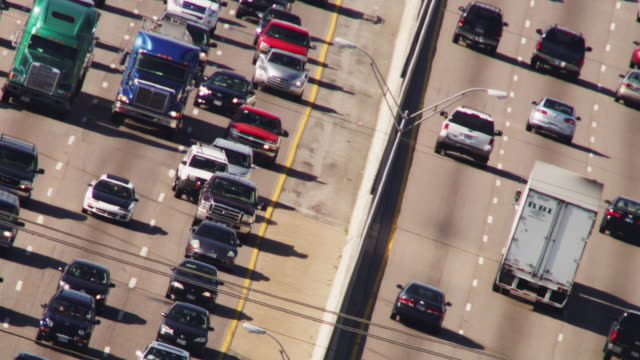 high titled angle featuring a mass of commuter traffic driving toward and away from camera. - block shape stock videos & royalty-free footage