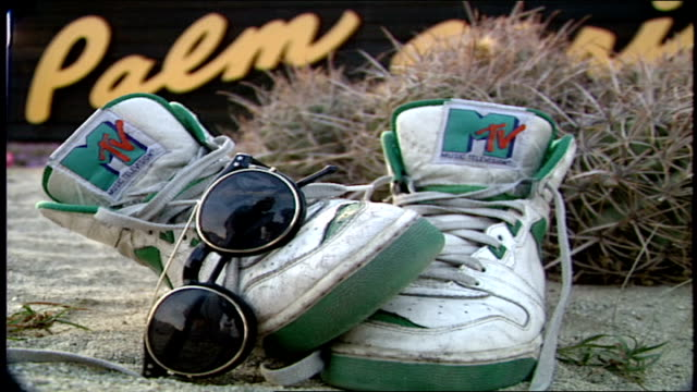 cu high top sneakers with mtv on tongue and sunglasses in palm springs california - mtv点の映像素材/bロール