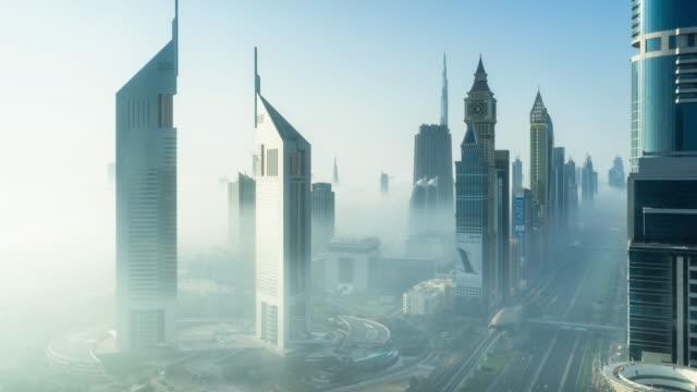 vidéos et rushes de high up view of dubai misty cityscape transition - quartier financier