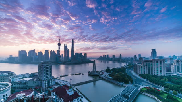 high up wide view of shanghai huangpu riverside city center dawn to morning glow transition - shanghai stock videos & royalty-free footage