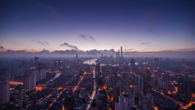 high up wide view of shanghai urban skyline dawn to day transition - dawn to day stock videos & royalty-free footage