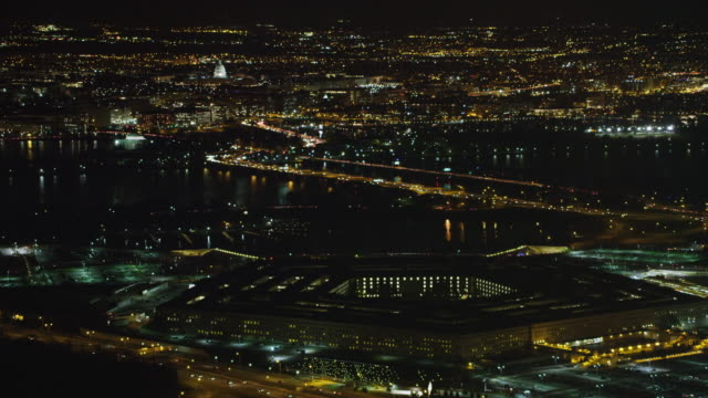 stockvideo's en b-roll-footage met high view of the pentagon at night with washington dc across potomac in background. shot in 2011. - ministerie van defensie