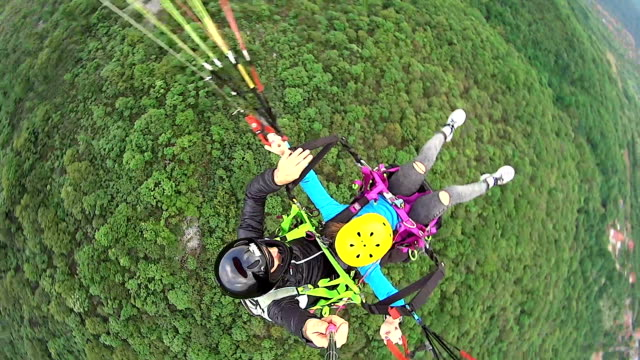 high view of woman doing tandem paragliding - paragliding stock videos & royalty-free footage