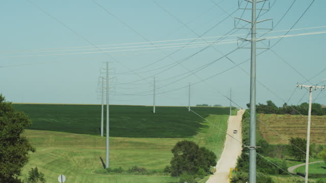 High voltage electrical wires, transformers and metal poles stretch into the distance across a rural landscape and country road.