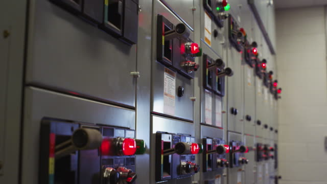 High voltage instrument panel at an electrical substation featuring levers and red lights.