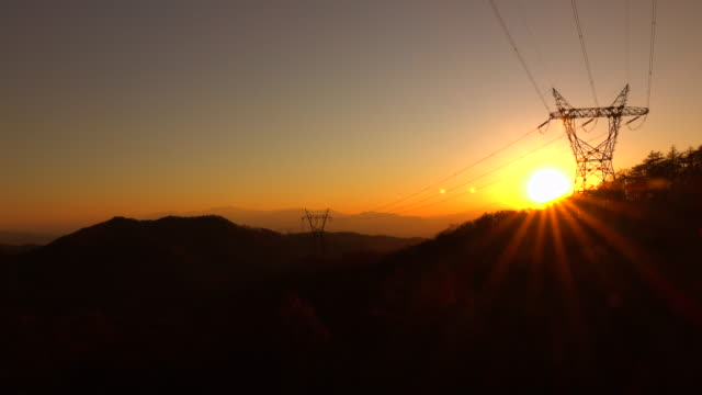 high voltage tower in mountains at sunset - electricity pylon stock videos & royalty-free footage