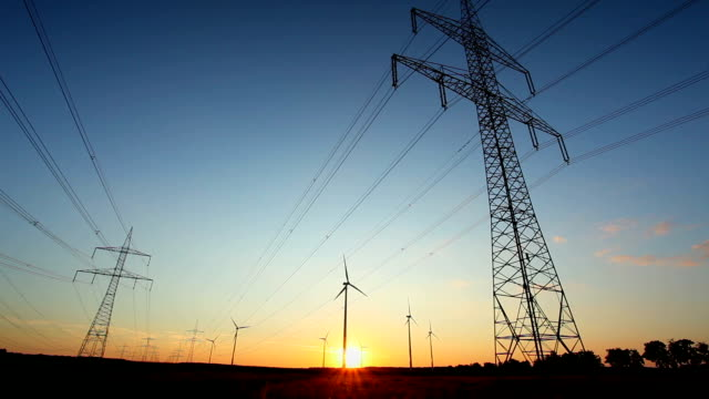 high voltage tower with windmills - sunset - synthpop stock videos & royalty-free footage