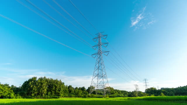 High voltage towers over paddy field with sky background time lapse