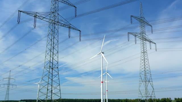 high voltage towers mit windturbinen - hochspannungsmast stock-videos und b-roll-filmmaterial