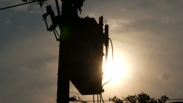 high voltage transformer with sunset background - conductor stock videos and b-roll footage