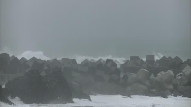 vídeos de stock, filmes e b-roll de high waves surge over the tetrapod/shot at muroto citykochi japan on august 92014 - quebra mar