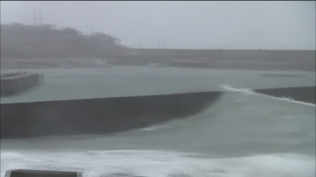 high waves surge toward the breakwater / typhoon no19 vongfong hit kagoshima on october 13 2014 and swept through the japanese archipelago over the... - fishing village stock videos and b-roll footage