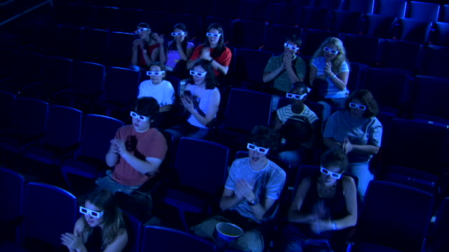 high wide angle of a movie theater audience clapping while watching a 3d movie. - biosalong bildbanksvideor och videomaterial från bakom kulisserna
