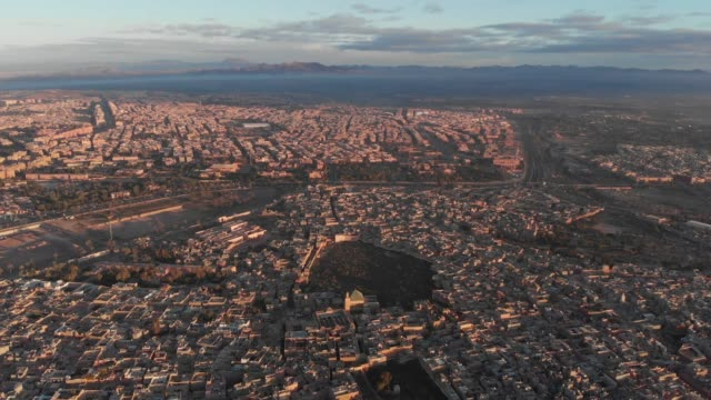 vídeos de stock e filmes b-roll de high wide drone shot of a moroccan city at sunset - marrocos