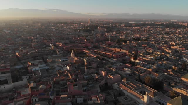 high wide drone shot of a moroccan city at sunset - town stock videos & royalty-free footage