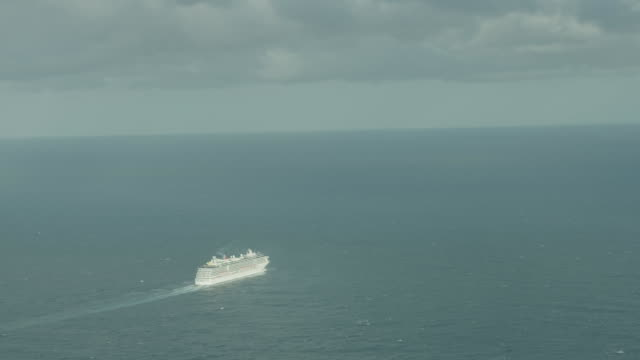 high wide shot drone aerial cruise ship sails on calm open ocean zoom in to the ship in mid distance zoom out and in with ship surrounded by open... - mid distance stock videos & royalty-free footage