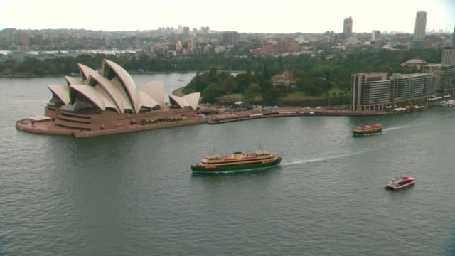 high wide shot point of view from sydney harbour bridge grey overcast day sydney opera house and circular quay cruise liner at international... - bennelong point stock videos and b-roll footage