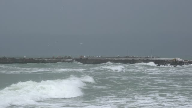 high winds and big waves breaking over a breakwater during a severe sea storm - 突堤点の映像素材/bロール