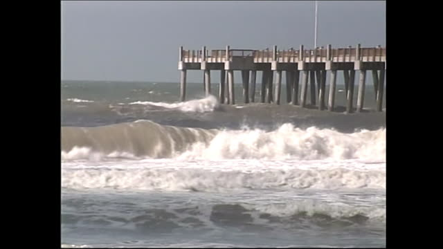 high winds and heavy surf with a pier in the background during hurricane dennis - environment or natural disaster or climate change or earthquake or hurricane or extreme weather or oil spill or volcano or tornado or flooding stock videos & royalty-free footage