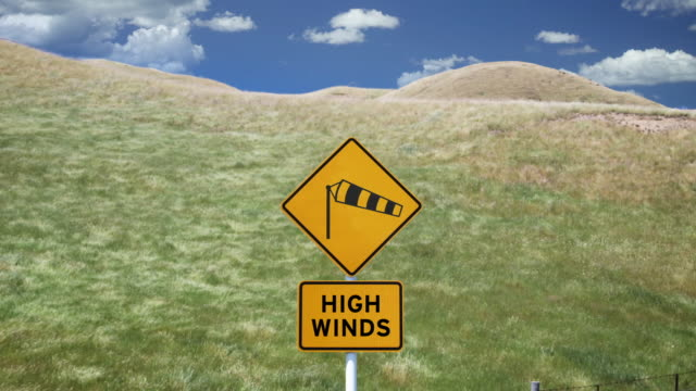 t/l, ws, 'high winds' sign with grass blowing on wind in background, blenheim, marlborough, new zealand - 強風点の映像素材/bロール