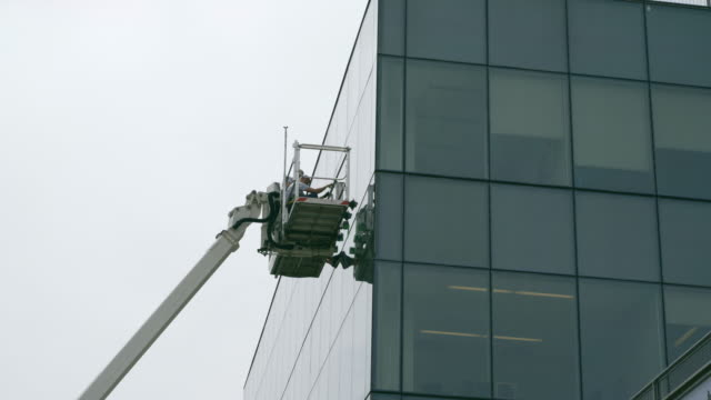high-altitude work. team of blue-collar workers inspecting the office building glass facade using the lifting platform. - hoisting stock videos & royalty-free footage