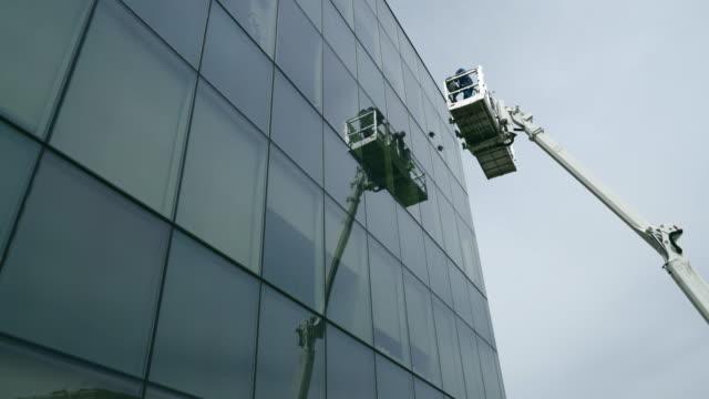 高地作業。持ち上げプラットフォームを使用してオフィスビルのガラスファサードを検査するブルーカラーの労働者のチーム。 - 交代点の映像素材/bロール