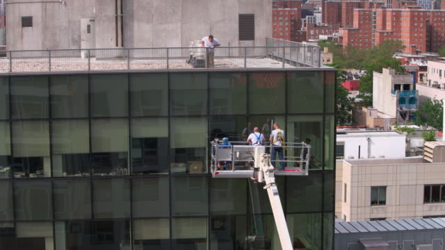 high-altitude work. two teams of blue-collar workers inspecting the office building glass facade: one team from outside using the lifting platform, and another from inside. - installing stock videos & royalty-free footage