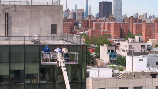 high-altitude work. two teams of blue-collar workers working on the office building glass facade: one team from outside using the lifting platform, and another from inside. - hoisting stock videos & royalty-free footage