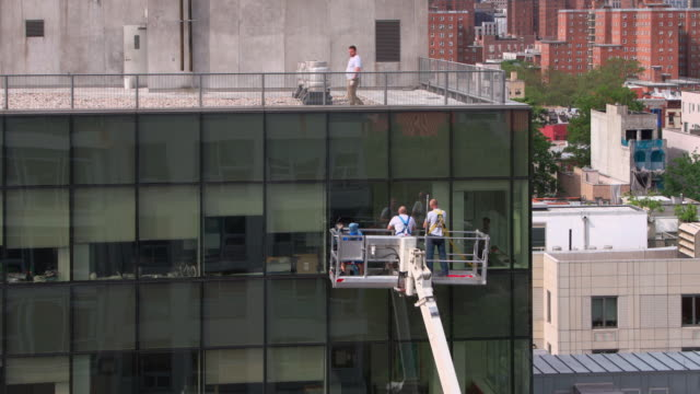 高地作業。オフィスビルのガラスファサードで働くブルーカラーの労働者の2つのチーム:持ち上げプラットフォームを使用して外部から1チーム、内側から別のチーム。 - オフショット点の映像素材/bロール