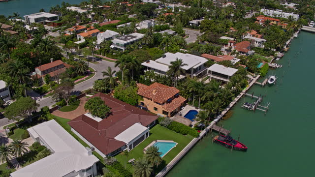 high-angle aerial view of residential houses on venetian islands, miami, florida. drone-made video with panning camera motion. - palm tree stock videos & royalty-free footage