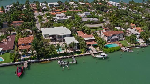 stockvideo's en b-roll-footage met hoge hoek luchtmening van woonhuizen op venetiaanse eilanden, miami, florida. drone-gemaakte video met panning camera beweging. - venetian causeway bridge