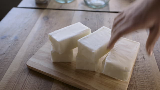 High-angle, close-up shot of blocks of lard being stacked into a pyramid shape, UK.